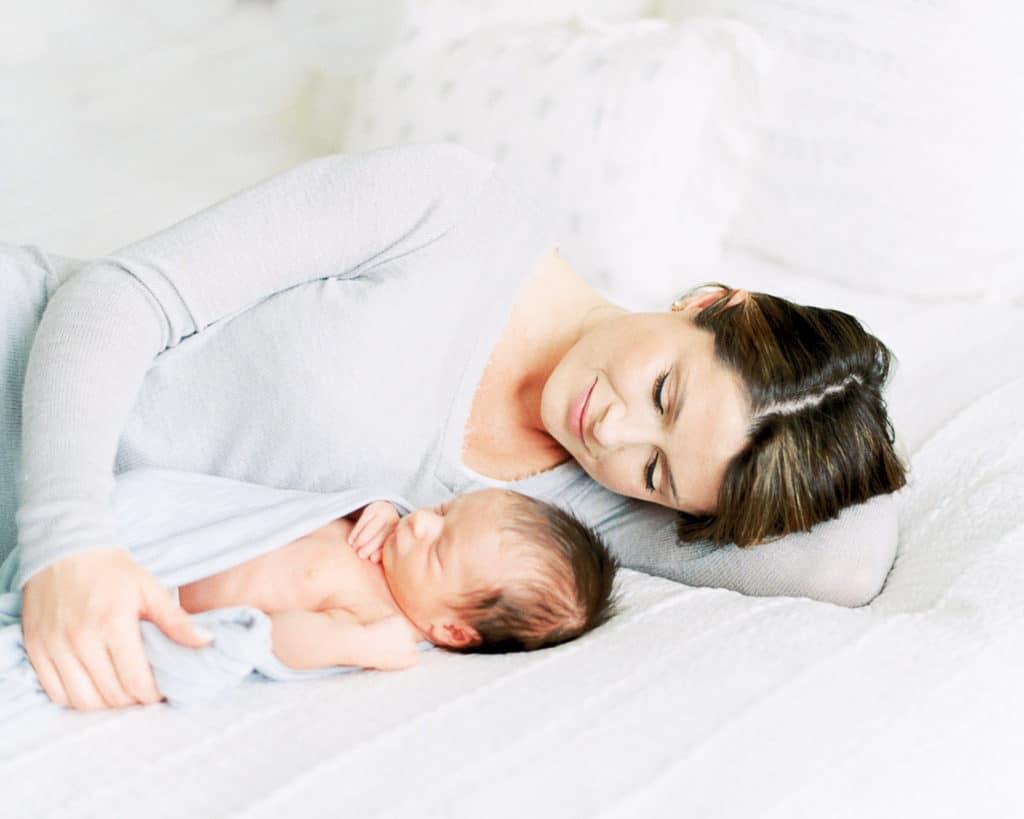Portrait of Mom snuggling newborn baby boy on bed
