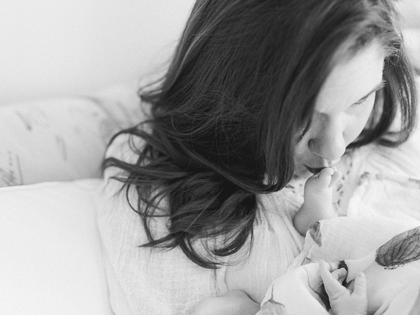 Portrait of Mom kissing newborn baby boy feet
