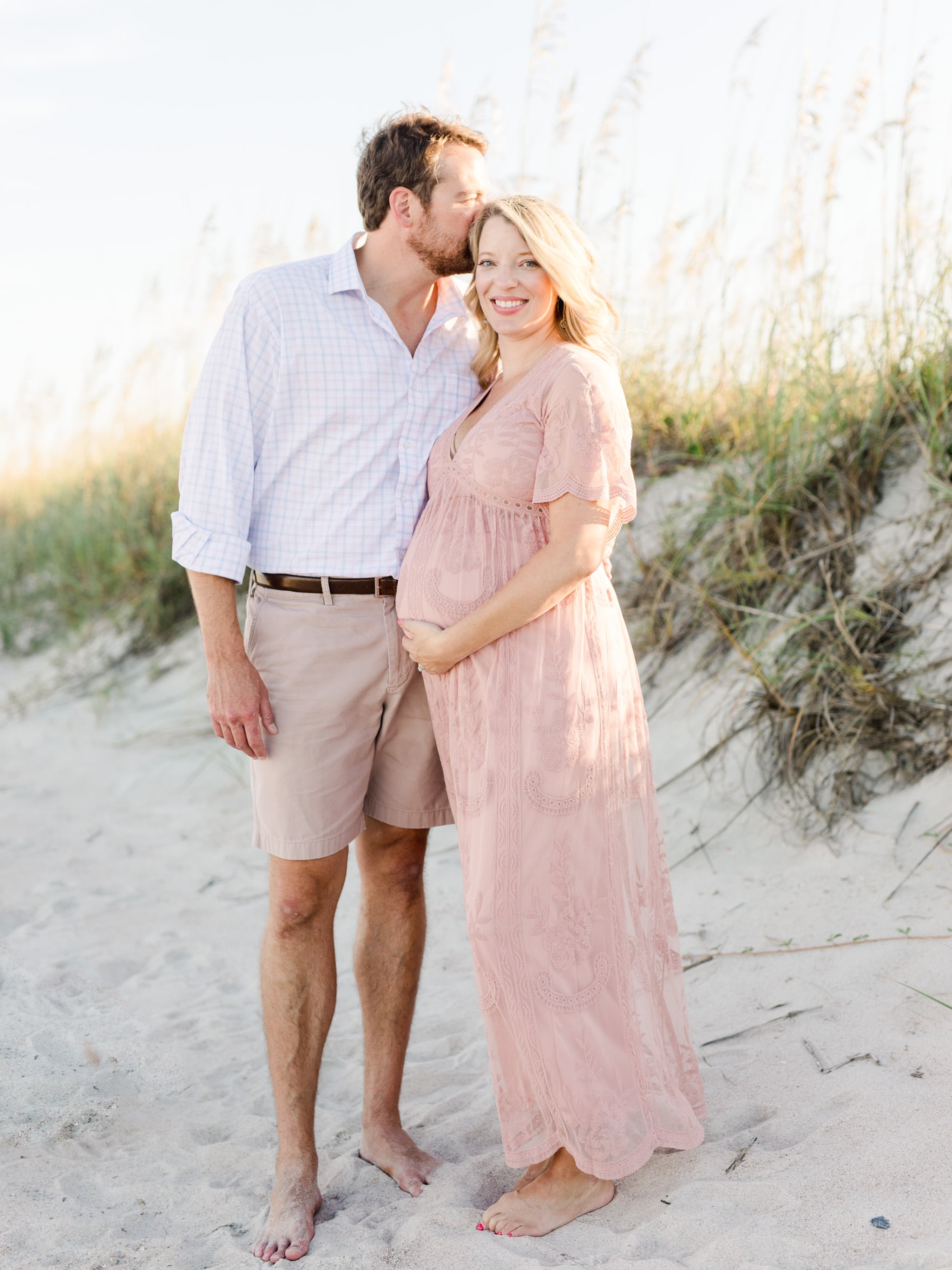 Mom and Dad taking maternity pictures, embracing on Tybee Island Georgia
